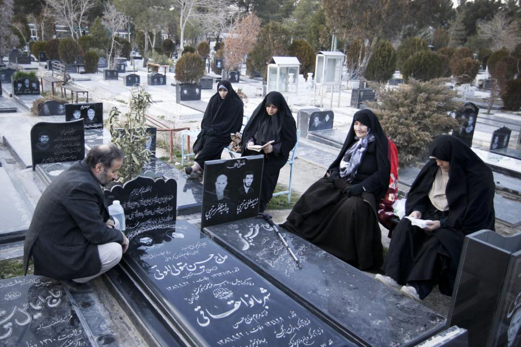 Behesht-e Zahra Tehran, An Iranian family prays next to the graves of their loved ones at ...