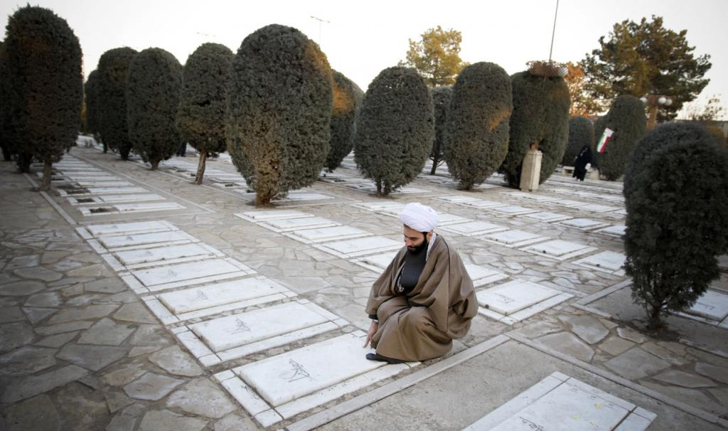 Behesht-e Zahra Tehran, An Iranian clergyman prays at the graves of soldiers who were ...
