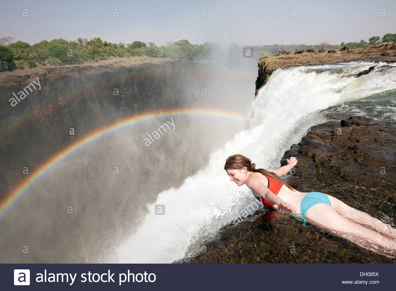 Devil's Pool Livingstone, A young woman hanging over the edge of the Victoria Falls in ...