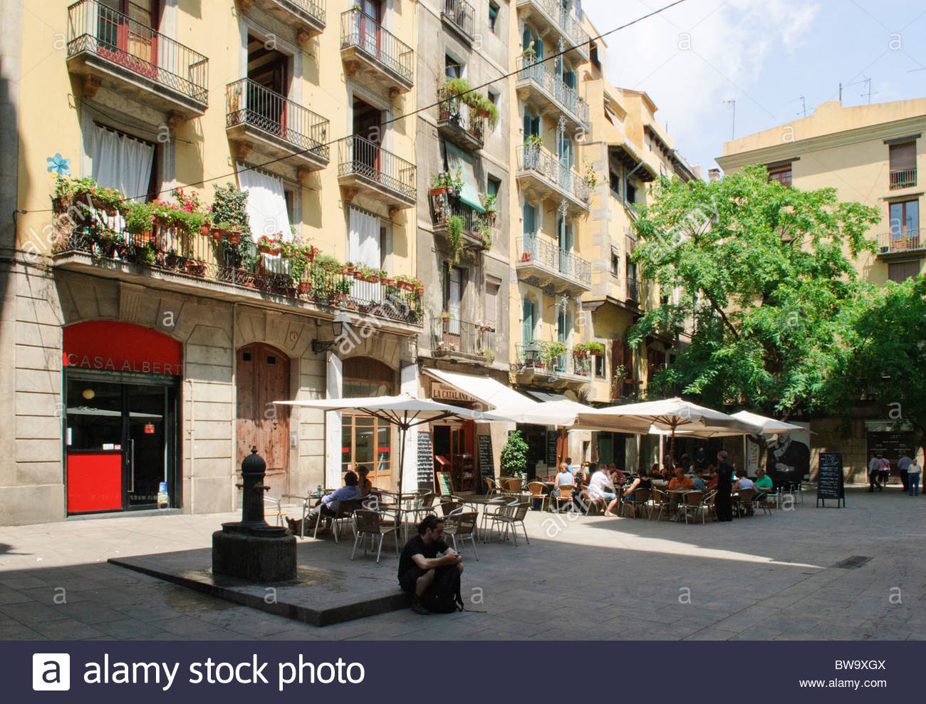 Plaça Sant Felip Neri Barcelona, people sit around outside tables on Plaza de les Olles square in ...