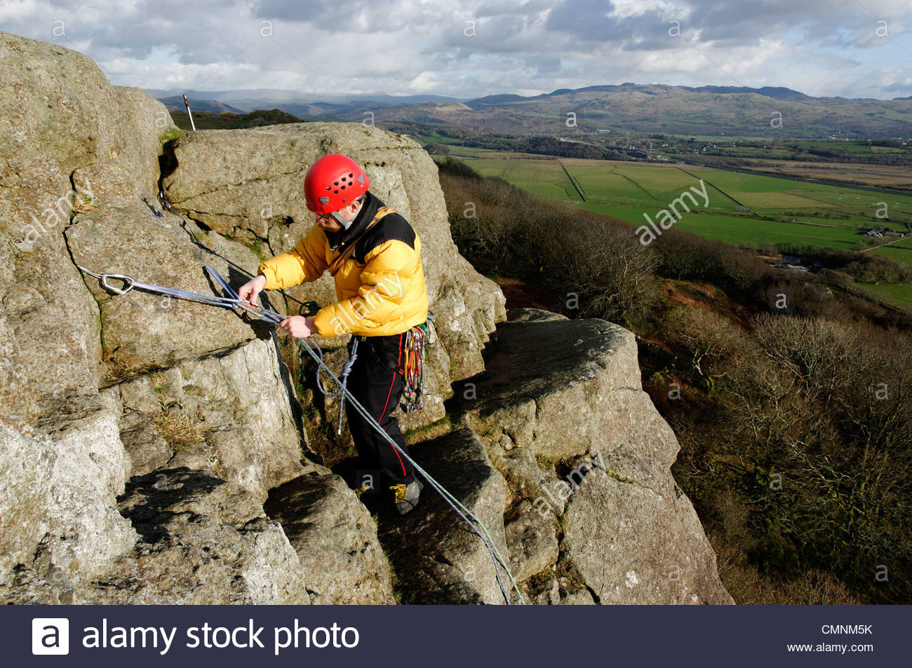 Tremadog North Wales, A rock climber building a belay at the Upper Tier of Tremadog ...