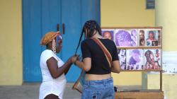 Makung Central Street Makung | Elderly Afro-American woman is making braids into hair to young ...