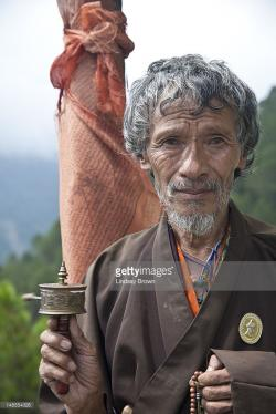 Prayer Wheel Mongar | Man With Prayer Beads And Prayer Wheel In Front Of Prayer Flag On ...