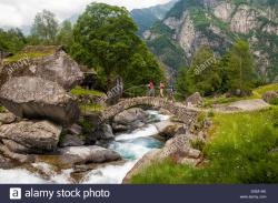 Val Bavona Valle Maggia | Three hikers crossing a medieval arch bridge, Puntid, Val ...
